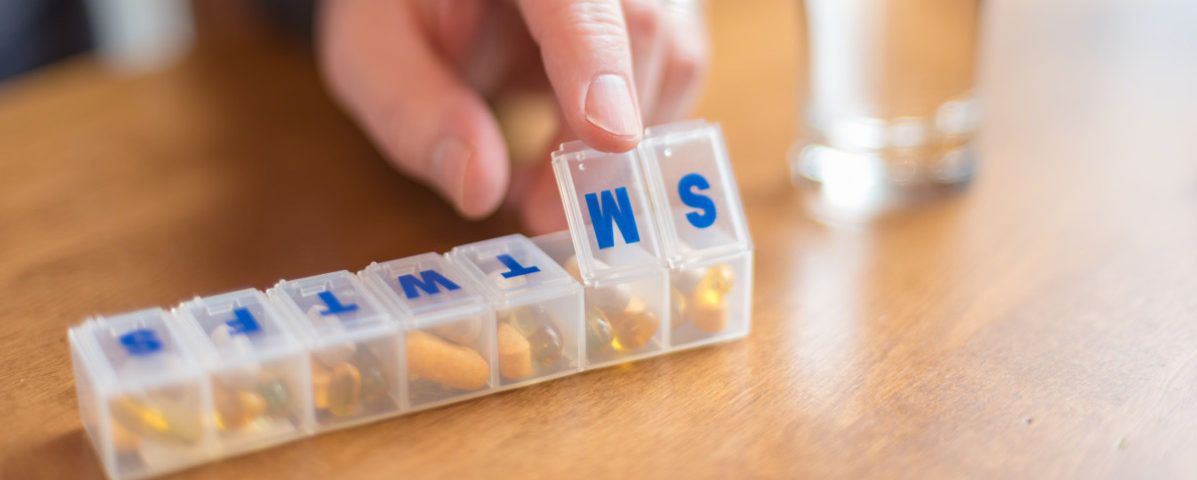 Man using a pill holder to organize daily vitamins and