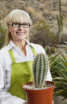 Portrait of a senior gardener holding potted cactus plant