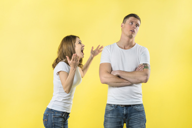young-woman-yelling-her-boyfriend-against-yellow-backdrop_23-2148056191
