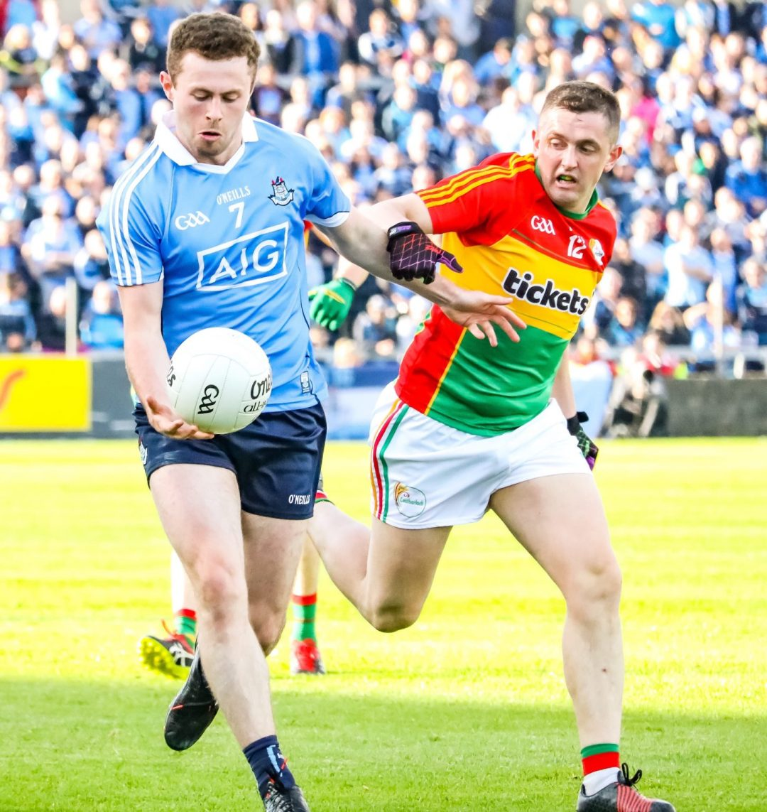 Dublin Player Jack McCaffrey In Sky Blue Jersey Breaking Away From a Carlow Player In a red yellow and green jersey during last year's Leinster Senior Football Championship