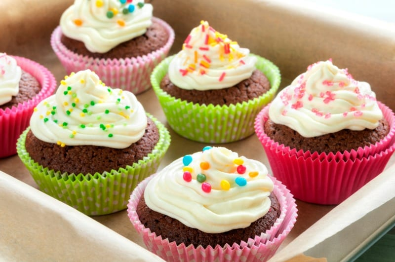 Fancy chocolate cupcakes with vanilla cream and colorful toppings and decoration