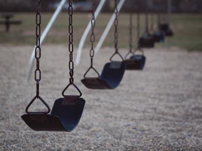 A set of empty black swings in a line