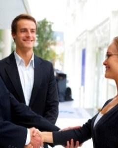 business men shaking womans hand featured