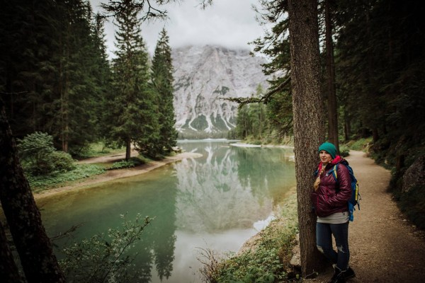 We Are The Wanderers editor Cat Ekkelboom-White leaning against a tree by Lake Prags in the Dolomites