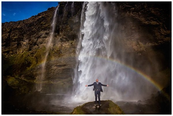 Mike stands with his arms outstretched to the sides in front of a large waterfall in Iceland