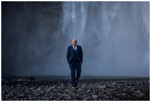 Mike walks away from Skogafoss waterfall wearing a blue suit