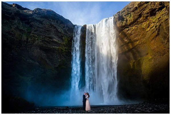 Anna and Mike embrace in front of Skogafoss waterfall