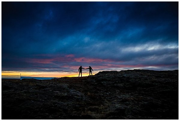 Silhouettes of Anna and Mike holding hands in front of a sunset in Iceland