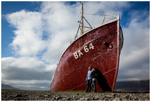 Anna and Mike lean against an old beached ship