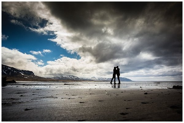 Silhouettes of Anna & Mike kissing on the black beach in Iceland