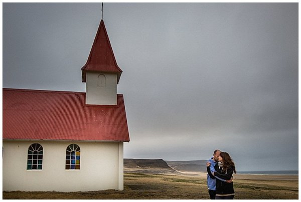 Anna and Mike stand in front of a white and red church in Iceland
