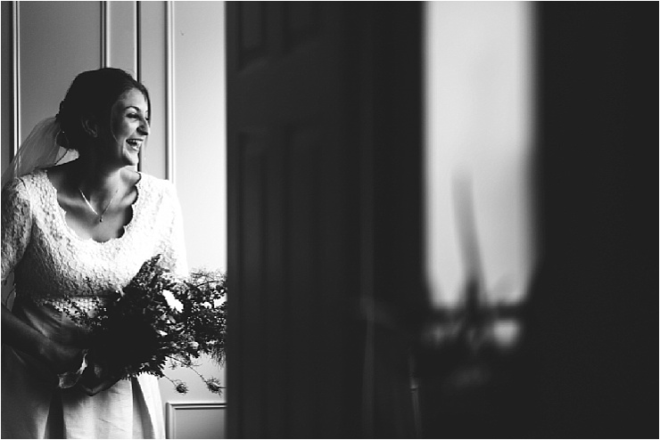 The bride Chloe looks out of a window and smiles by Hannah Hall Photography