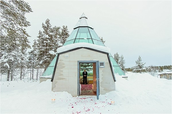 The groom waits inside the glass kota for his bride at Kakslauttanen arctic resort in Finland by Your Adventure Wedding