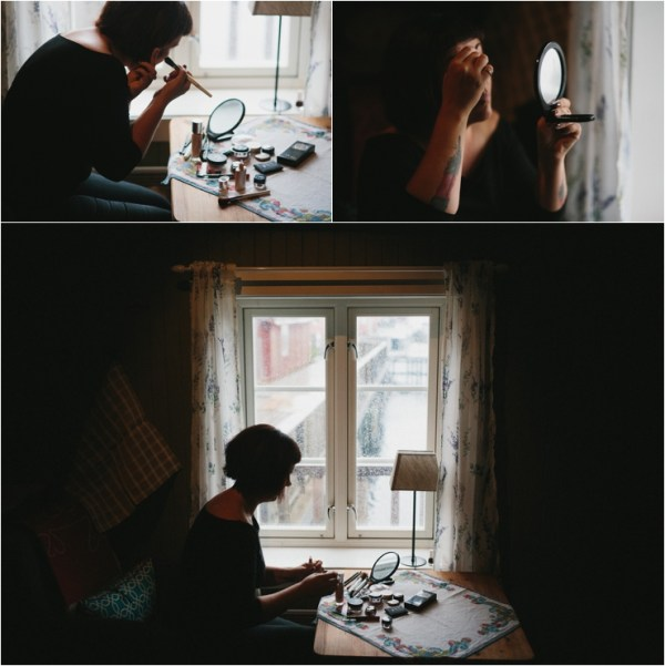 The bride Maz sits in front of a window to do her makeup for her elopement in Lofoten Norway by Thomas Stewart