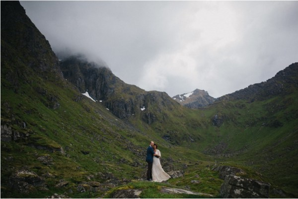 The bride's dress blows in the wind in the dramatic elopement in Lofoten Norway by Thomas Stewart