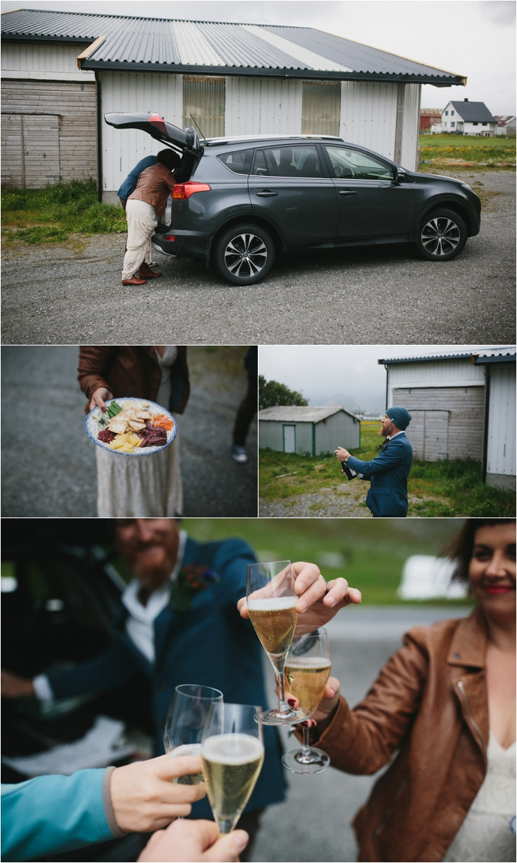 The bride and groom celebrate their elopement with snacks and champagne from the back of their car in Lofoten Norway by Thomas Stewart