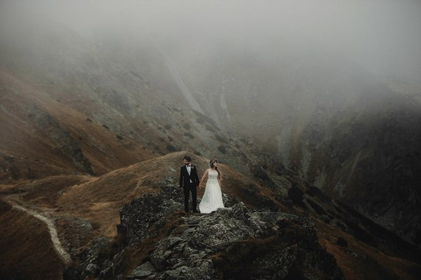 After-Wedding Shoot In The Tatra Mountains In Poland couple standing on a misty mountain by Fotomagoria