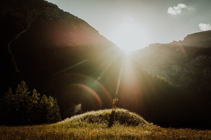 Couple stands on a hilltop at sunset in an adventure session in the Austrian Alps by Wild Connections Photography