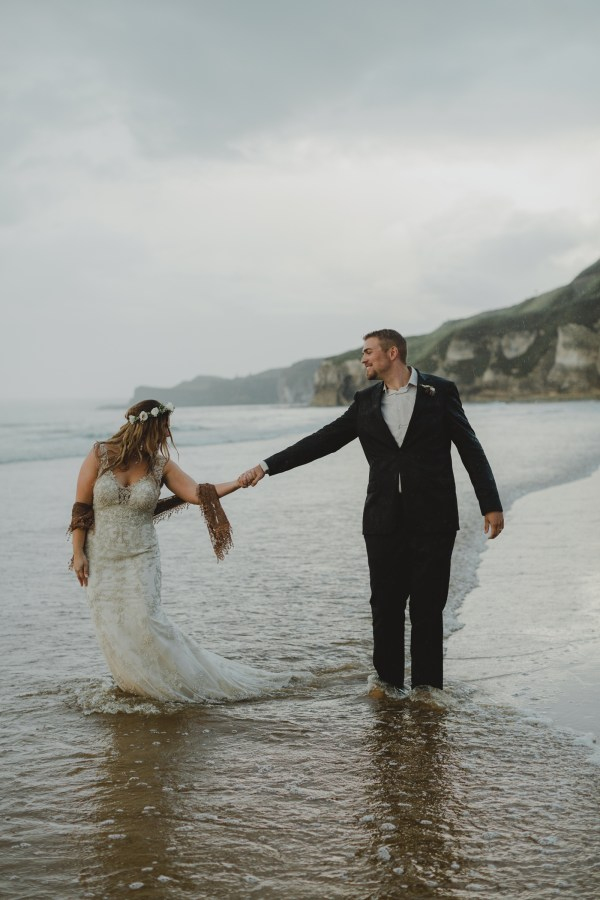Bride and groom walk through the water on the beach in Northern Ireland by Paula O'Hara