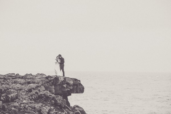 Bride and groom stand on a cliff edge in Iceland By Projectphoto.ch