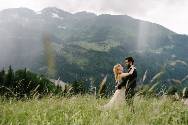 Bride and groom embrace in the long grass - After wedding honeymoon shoot in Wengen by Caroline Hancox Photography