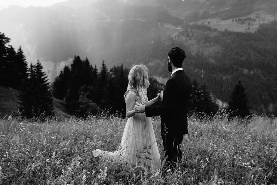 Sunbeams shine through the clouds as the bride and groom stand in the long grass - After wedding honeymoon shoot in Wengen by Caroline Hancox Photography