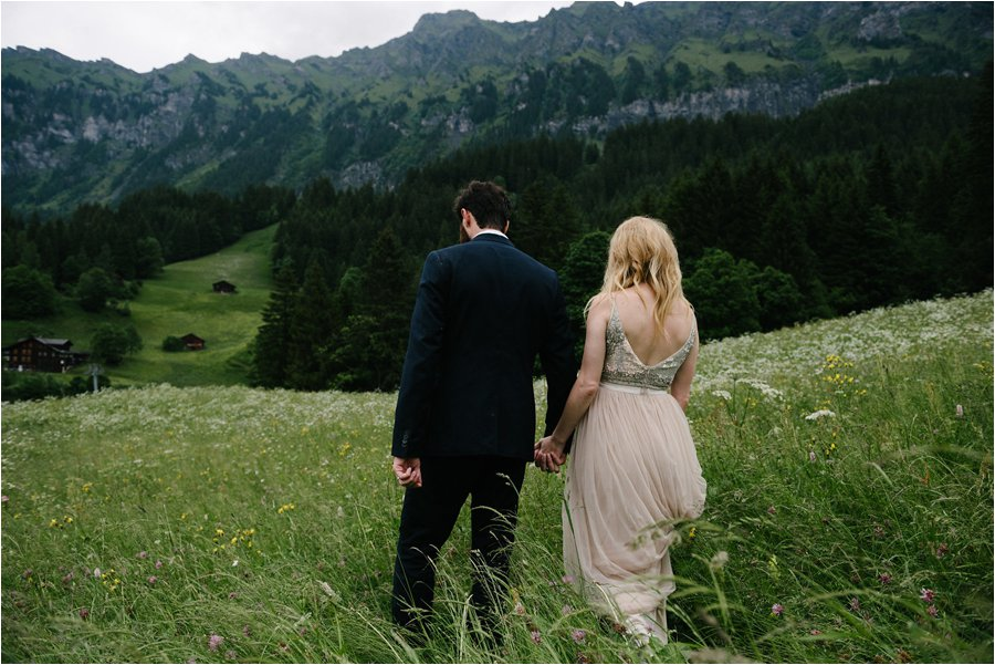 Bride and groom walk through the long grass meadows - After wedding honeymoon shoot in Wengen by Caroline Hancox Photography
