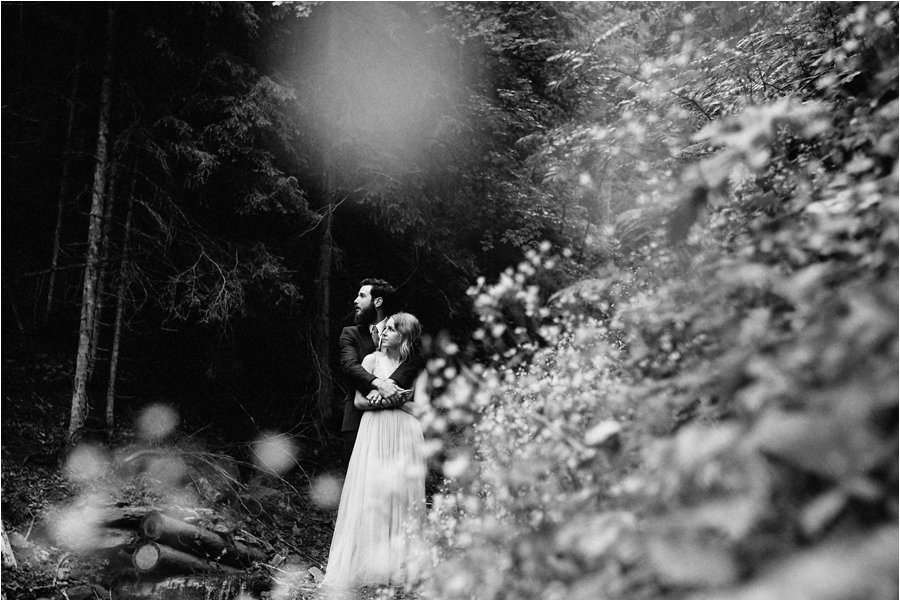 A picture of the bride and groom in a forest photographed through some wild flowers - After wedding honeymoon shoot in Wengen by Caroline Hancox Photography