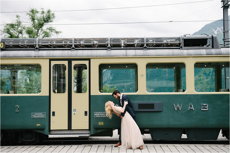 Bride and groom pose by the Wengen Alp Bahn Train - After wedding honeymoon shoot in Wengen by Caroline Hancox Photography