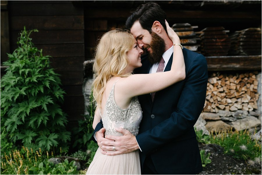 Bride and groom embrace in front of a wooden chalet in Switzerland - After wedding honeymoon shoot in Wengen by Caroline Hancox Photography