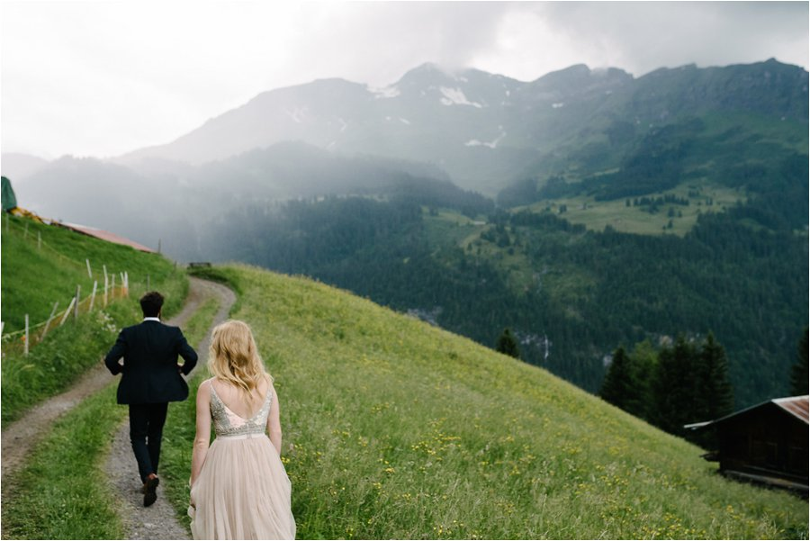 Bride and groom walk down a dirt road through the meadows - After wedding honeymoon shoot in Wengen by Caroline Hancox Photography