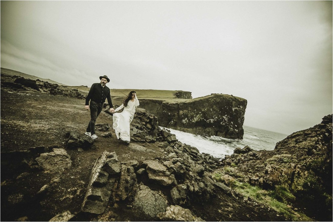 The wind blows Gaby's dress as she walks along the cliffside for their Iceland anniversary shoot by Projectphoto.ch