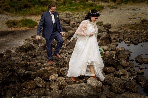The bride and groom climb over rocks to get to their elopement location on Loch Coruisk by Lynne Kennedy Photography
