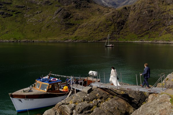 Tina & Jürgen return to the boat to take them back after their Isle of Skye elopement by Lynne Kennedy Photography