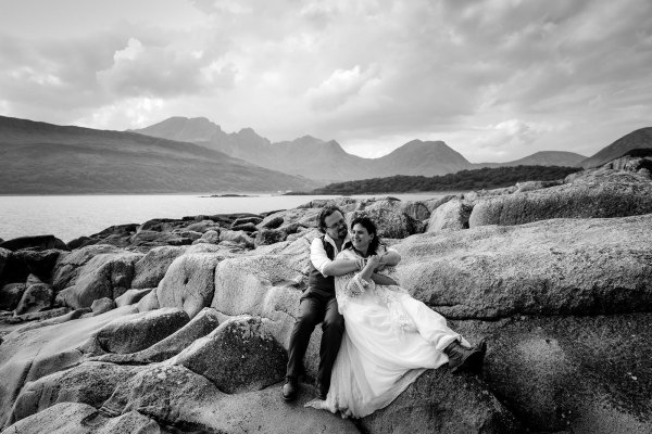 Black & white image of Tina & Jürgen embracing on some rocks by the shores of the Loch by Lynne Kennedy Photography