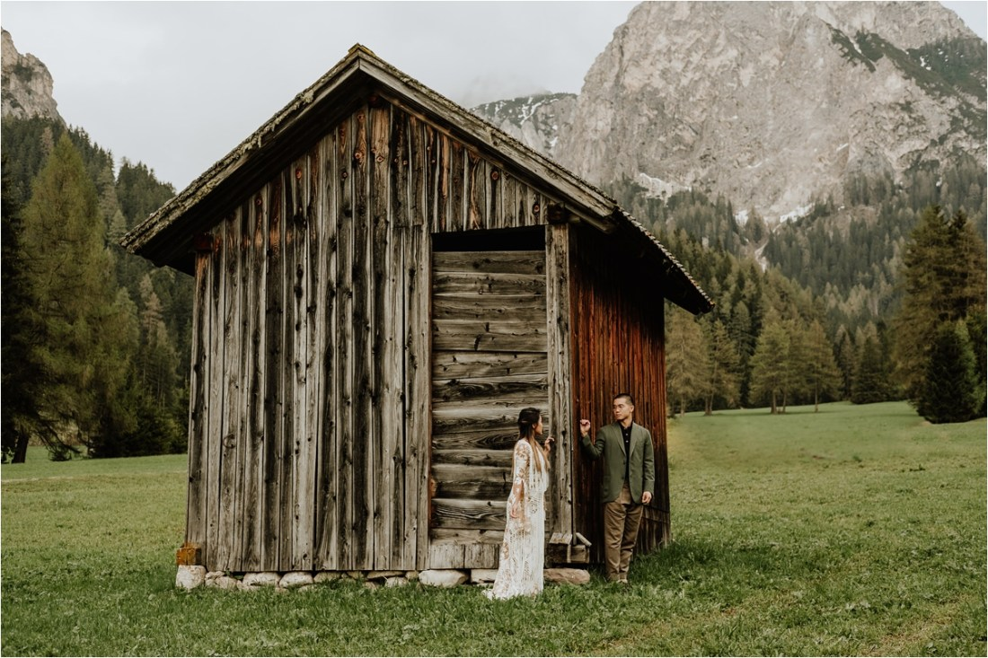 Christina & Ted by a wooden hut in the Dolomites by Wild Connections Photography