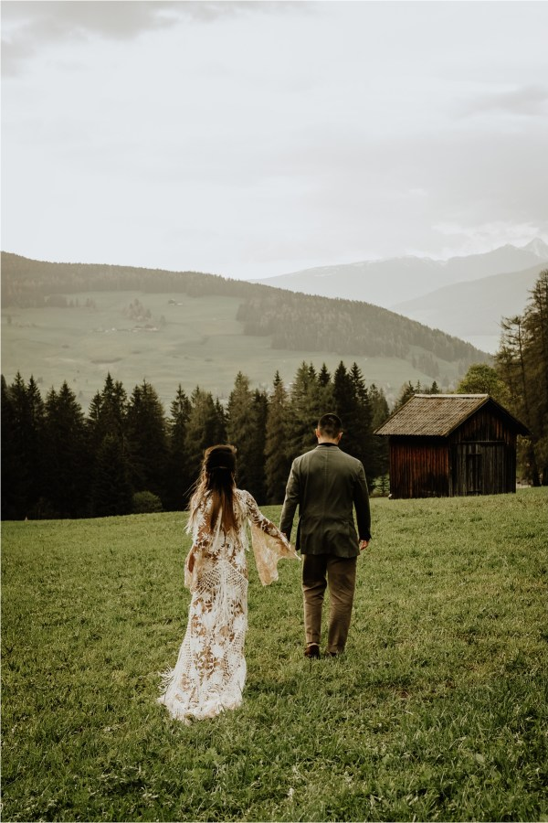 Christina & Ted walk through the meadows in the Dolomites by Wild Connections Photography
