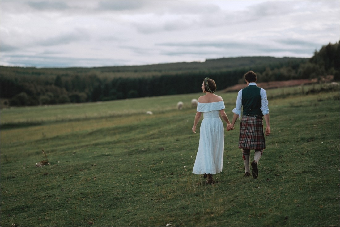 Bride & Groom walk across an open field on a sheep farm by Fox & Bear Photography
