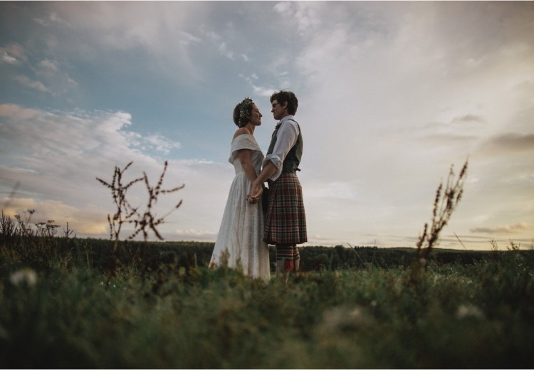 The bride and groom face each other in a field on a sheep farm in Scotland by Fox & Bear Photography