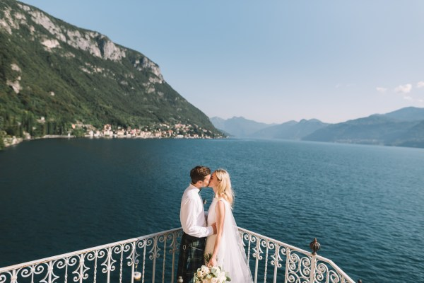 Bride and groom kiss on a balcony by Lake Como Wedding Photographer Lucie Watson Photography