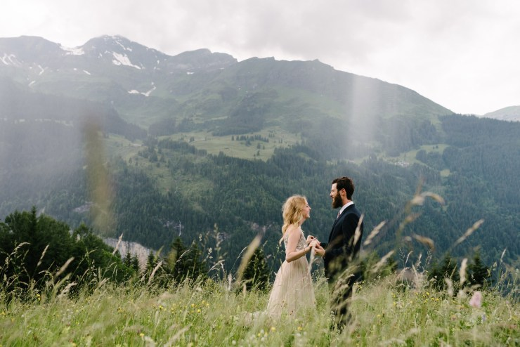 Bride and groom in a meadow in Wengen Switzerland by Caroline Hancox Photography