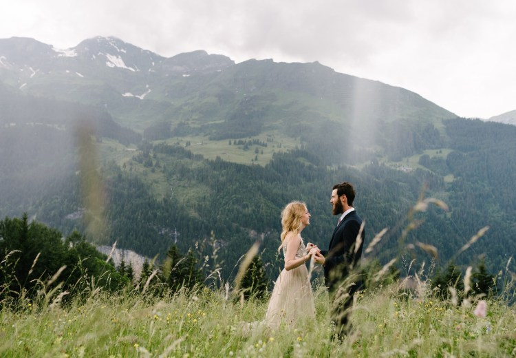 Bride and groom in a meadow in Wengen Switzerland by Caroline Hancox Photography