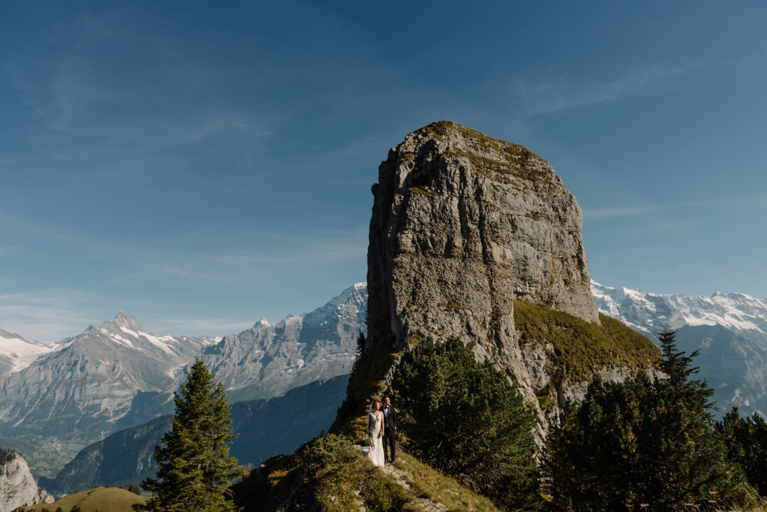 A tall rock face with a bride and groom standing at the bottom by Caroline Hancox Photography