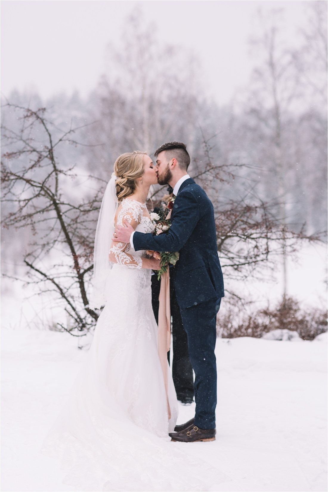 The first kiss after a winter wedding in the snow in Finland by Lucie Watson Photography