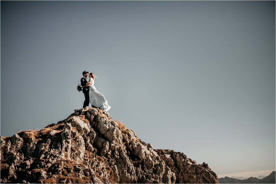 Bride and groom stand on a mountain peak with the bride in a blue dress which blows in the wind by Aneta Lehotska