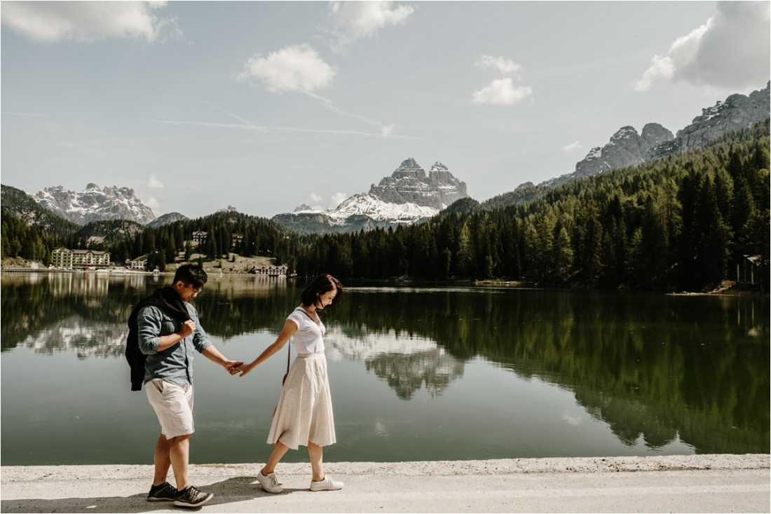 A Chinese couple walk hand in hand around a lake in the Italian Alps by Wild Connections Photography