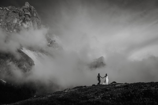 Black and white image of a bride and groom hiking elopement in the Dolomites in Italy by Wild Connections Photography