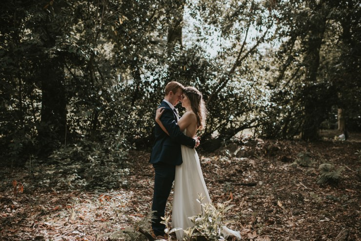 Bride and groom embrace in a woods by Louise Scott Photography