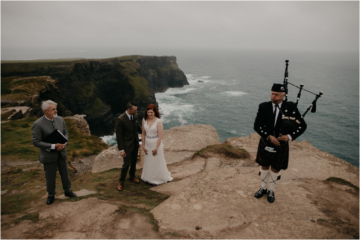 Cliff top Hand fasting of Jon and Sara, on the Cliffs of Moher, Co Clare, Ireland Captured by Photographers Seandkate the bride and groom listen to a bagpiper on the cliff edge