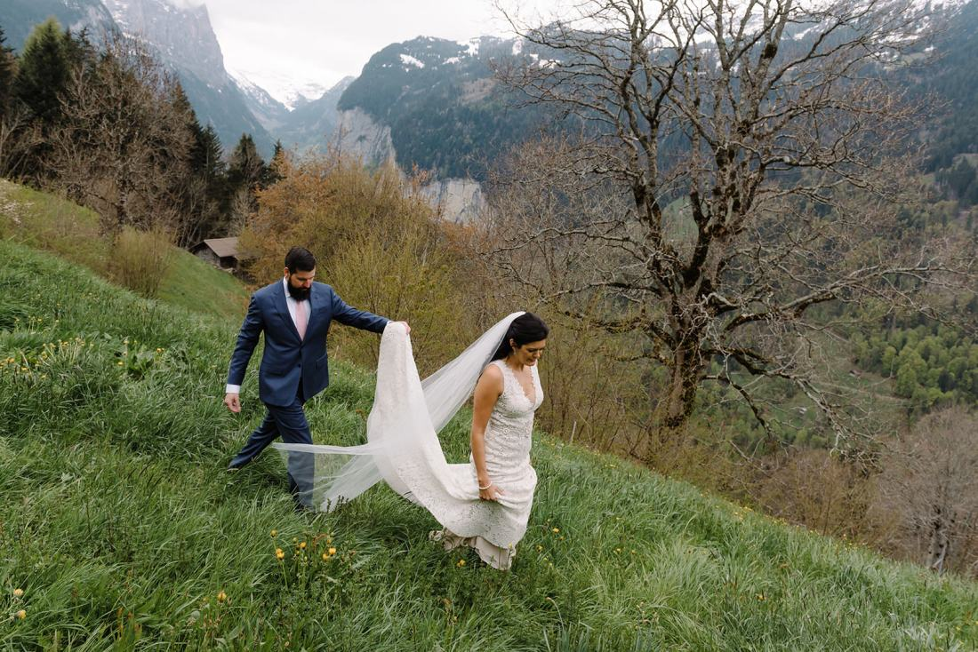 Bride & groom walk through Swiss meadows